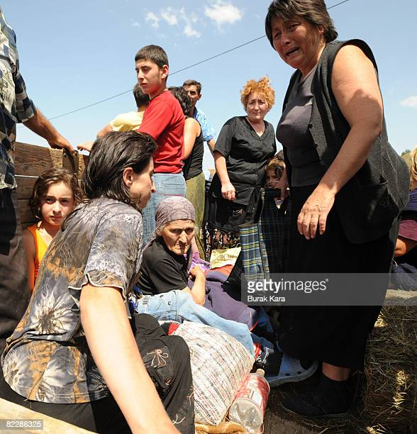 People get on the back of a truck as they flee from the town of Gori on August 13 in Georgia According to eye witness reports villages in Georgia...