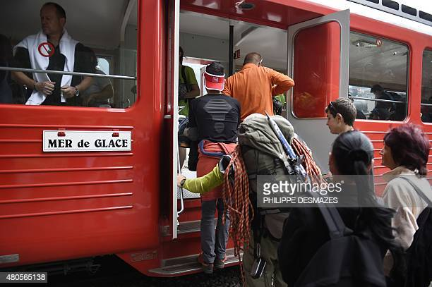 People get on the famous little red railway train of Montenvers on June 8 2015 at the railway station in Chamonix MontBlanc eastern France 'La mer de...
