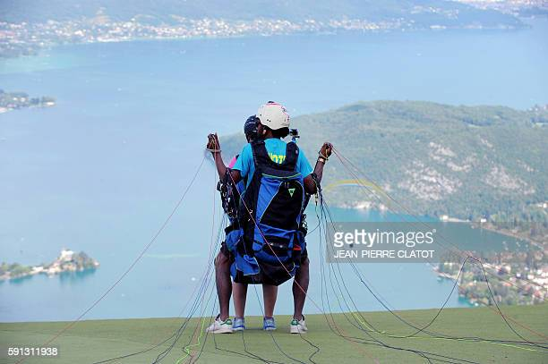 People get ready for a paragliding flight above the Annecy lake in the au Col de la Forclaz near Montmin in Savoy French Alps on August 17 2016 where...