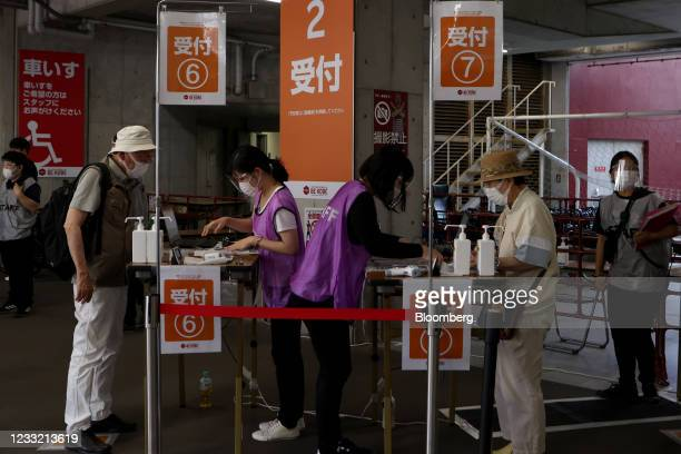 People get their documents check prior to receiving a dose of the Pfizer-BioNTech Covid-19 vaccine at a mass inoculation site at Noevir Stadium Kobe...
