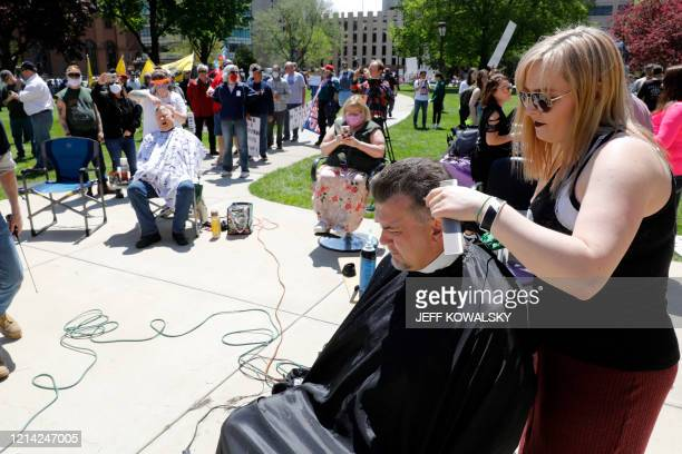 People get their hair cut at the Michigan Conservative Coalition organized Operation Haircut outside the Michigan State Capitol in Lansing Michigan...