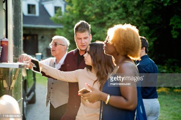 """people getting meals from a food truck at a wedding. - """"martine doucet"""" or martinedoucet stock pictures, royalty-free photos & images"""