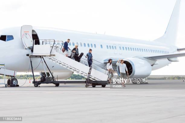 people getting off an airplane - arrival stock pictures, royalty-free photos & images