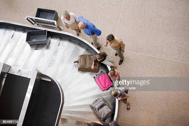 People getting their suitcases from a suitcase