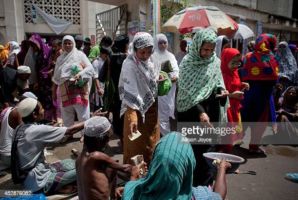 People give alms to beggars after prayer at the National Mosque Baitul Mukarram during Eid alFitr on July 29 2014 in Dhaka Bangladesh Muslims around...