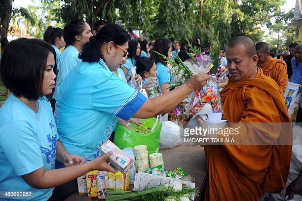 People give offerings to Buddhist monks and to mark Queen Sirikit's birthday in Thailand's southern province of Narathiwat on August 12 2015 The...