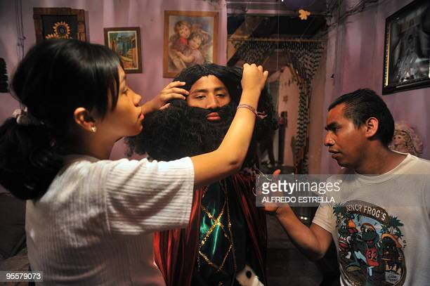 People give the finishing touches to the false beard of 'Gaspar' during the preparation of the Three Wise Men in Mexico City's Guerrero neighbourhood...