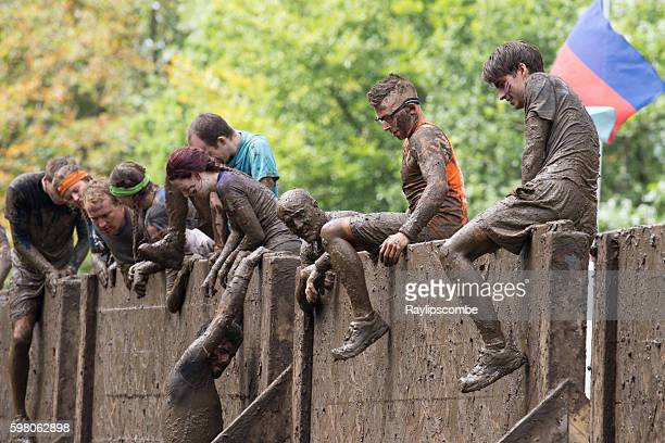People giving each other a (muddy) helping hand