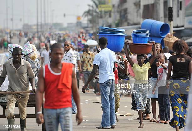 People go about their daily lives in Abidjan on December 29 2010 Ivory Coast strongman Laurent Gbagbo's most notorious street lieutenant vowed that...