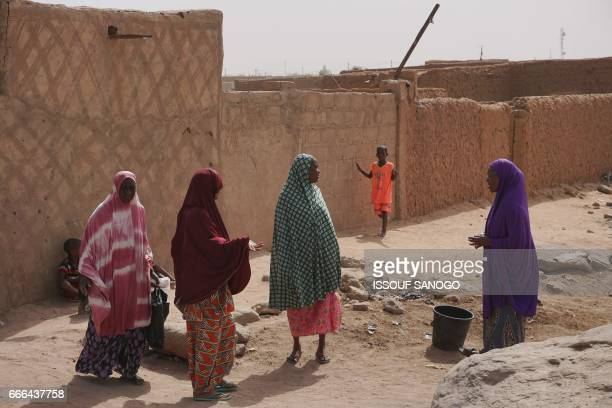 People go about their daily lives on a street in Agadez northern Niger on April 6 2017 Agadez the gateway to the desert a crossroads where thousands...