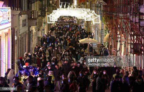 People go about Via dei Condotti in central Rome for their Christmas shopping on December 13 during the COVID-19 pandemic caused by the novel...