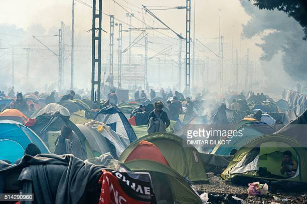 People go about with their daily life among tents on a foggy morning at a makeshift camp at the GreekMacedonian border near the Greek village of...
