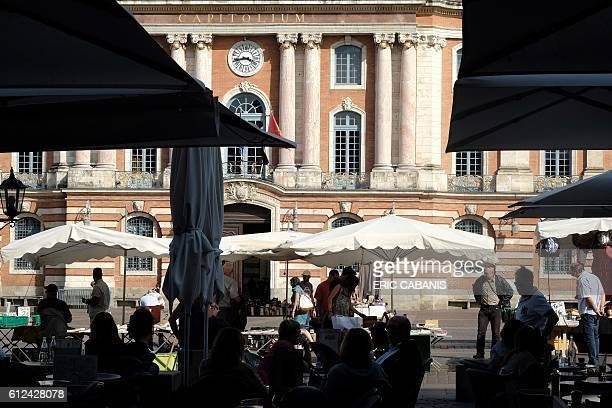 People go about with their dailylife by the city hall building at the place du Capitole in Toulouse on October 4 2016 / AFP / ERIC CABANIS