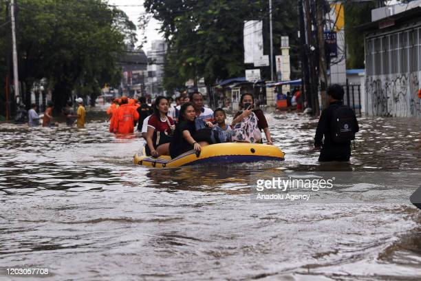 People go on a boat on flood waters after heavy rains hit Jakarta, Indonesia on February 25, 2020.