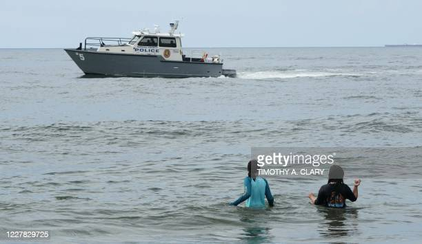 People go out in the ocean as a Nassau County Police Marine Unit boat patrols the waters at Nickerson Beach Park in Lido Beach New York on July 29...