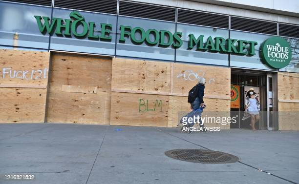 People go shopping at a Whole Foods Market store, which is boarded up after a night of protest over the death of African-American man George Floyd in...