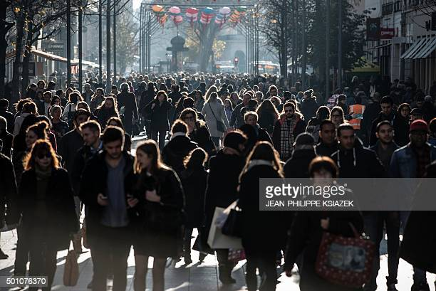 People go shopping on December 12 2015 in the center of the southeastern French city of Lyon 12 days before Christmas / AFP / JEANPHILIPPE KSIAZEK