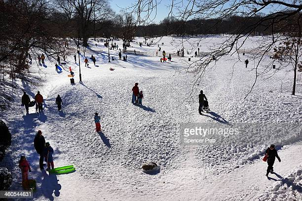 People go sledding following a snow storm in Prospect Park January 4, 2014 in the Brooklyn borough of New York City. The major winter snowstorm named...