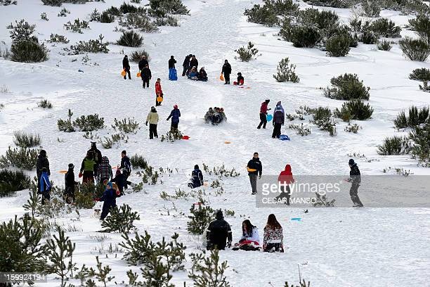 People go sledging after a snowfall in Pineda de la Sierra, near Burgos, on January 23, 2013. AFP PHOTO/ CESAR MANSO
