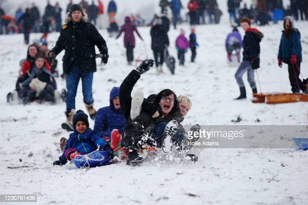 People go sledging in the snow on Parliament Hill on Hampstead Heath on January 24, 2021 in London, United Kingdom. Parts of the country saw snow and...