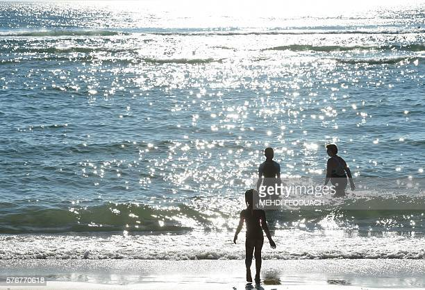 People go to swim in the sea on July 17 2016 in Biscarrosse southwestern France / AFP / Mehdi FEDOUACH