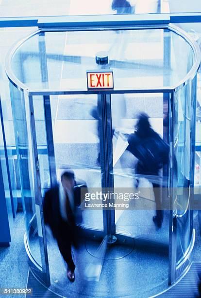 People Going Through Revolving Door