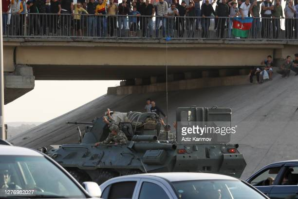 People greet Azerbaijani service members in military vehicles on September 27, 2020 in Baku, Azerbaijan. Since July there has been rising tensions on...