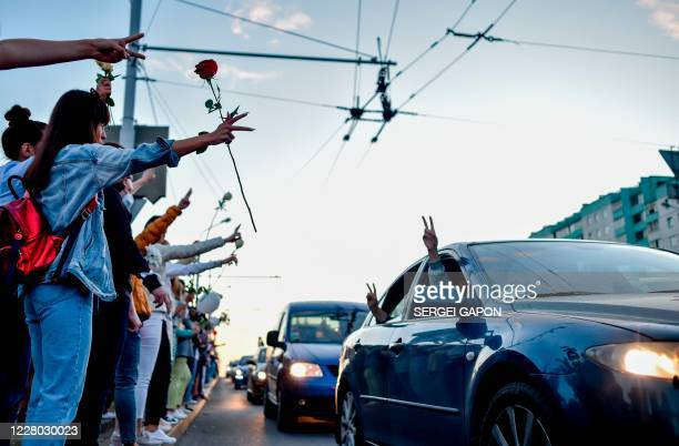 People greet each other making a Victory sign as they protest against police violence during recent rallies of opposition supporters, who accuse...