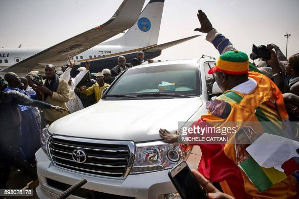 TOPSHOT People greet former president Amadou Toumani Toure as he disembarks from a plane in Bamako on December 24 as he returns for the first time to...