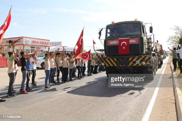 People greet Turkish Armed Forces' military vehicles including, tanks and armoured vehicles, which are being deployed to Syrian border to support the...