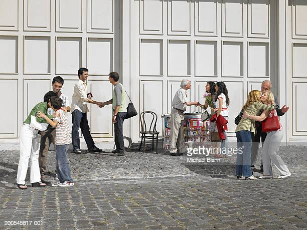 People greeting each other in busy street