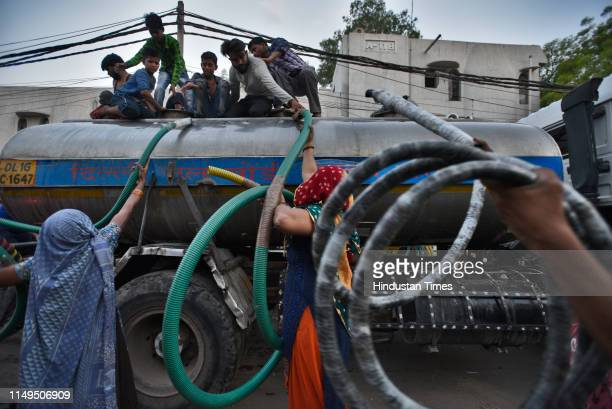 People hand over lengths of hose pipe to be used to fill water that will be used for drinking, bathing and washing, from a Delhi Jal Board tanker, at...