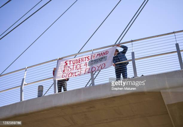 People hang a banner calling for justice for George Floyd on a bridge over Hiawatha Avenue on April 1, 2021 in Minneapolis, Minnesota. The Derek...