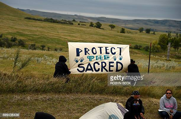 People hang a sign near a burial ground sacred site that was disturbed by bulldozers building the Dakota Access Pipeline near the encampment where...
