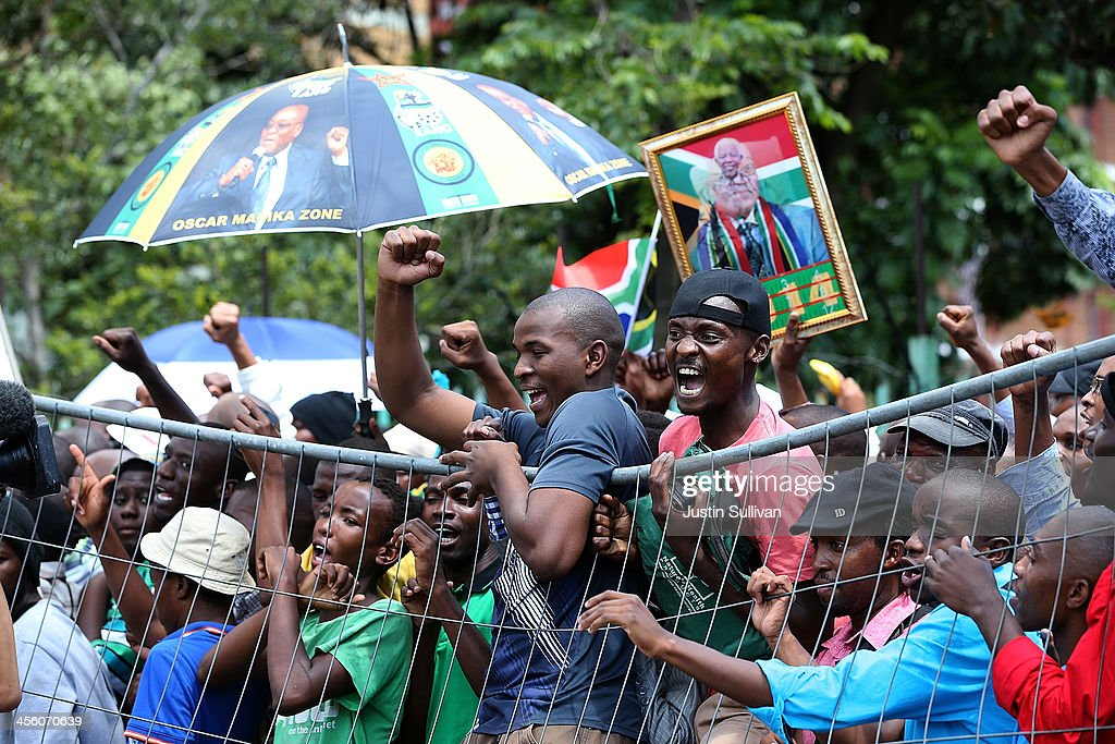 People hang from a fence as they protest outside of the Union Buildings after being told that they would not be allowed access to view the body of former South African president Nelson Mandela as he lies in state on December 13, 2013 in Pretoria, South Africa. Nelson Mandela's body will lie in state for three days as part of a week of events commemorating the life of former South African President. Mr Mandela passed away on the evening of December 5, 2013 at his home in Houghton at the age of 95. Mandela became South Africa's first black president in 1994 after spending 27 years in jail for his activism against apartheid in a racially-divided South Africa.