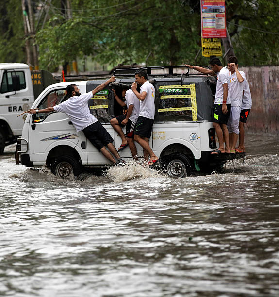 People hang on van to commute as roads are flooded with water during the heavy rainfall on June 21 2016 in Jammu India According to Skymet Weather...