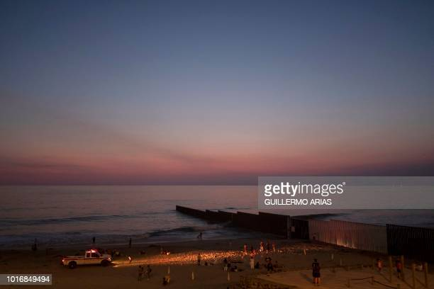 People hang out at the beach near the US/Mexico border fence in Playas de Tijuana Baja California state Mexico on August 10 2018 From the south...