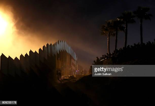 People hang out next to the USMexican border fence at Playas de Tijuana during a Fourth of July gathering on the beach on July 4 2017 in Tijuana...