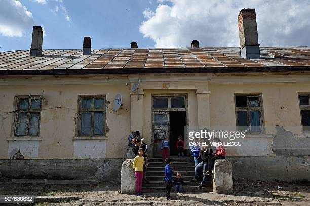 People hang out together in front of the abandoned building where Lorena and her child live in a village near Botosani, north-eastern Romania, on...