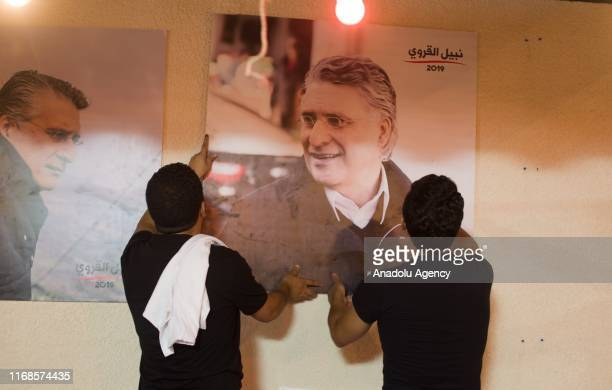 People hang the images of jailed President candidate Nabil Karoui of Qalb Tounes party at party headquarters in the Tunisian capital Tunis on...