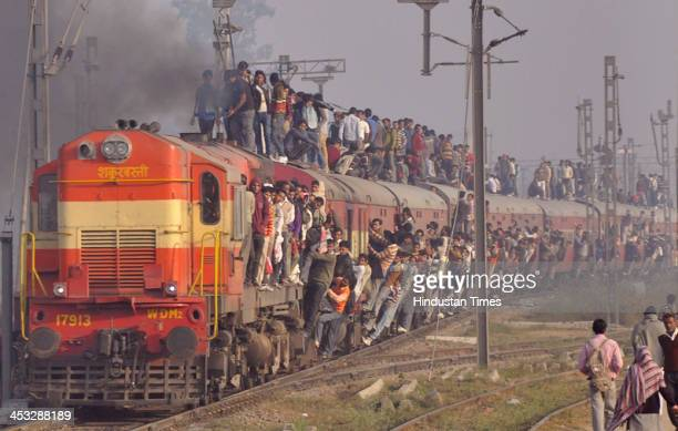 People hanging and travelling on roof of a overloaded passenger train near Loni Railway Station on December 2 2013 in Ghaziabad India Despite several...