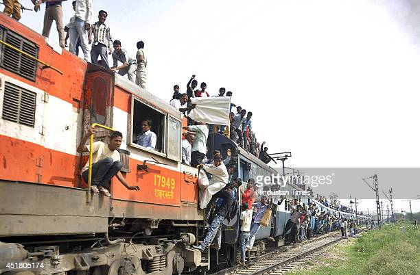 People hanging and travelling on the roof of an overloaded passenger train near Loni Railway Station on July 7 2014 in Ghaziabad India Despite...