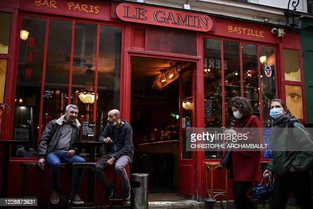 People have a drink as they sit on the terrace of a bar in the French capital Paris on October 3, 2020. - French authorities may place Paris on...