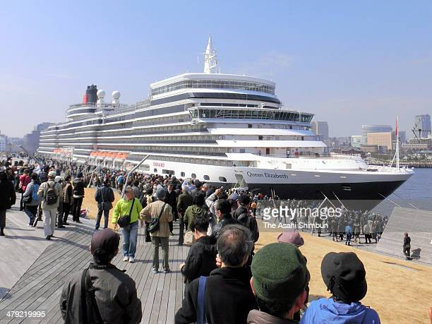 People have a look at the massive luxury ocean liner the Queen Elizabeth arrives at Yokohama port on March 17 2014 in Yokohama Kanagawa Japan The...