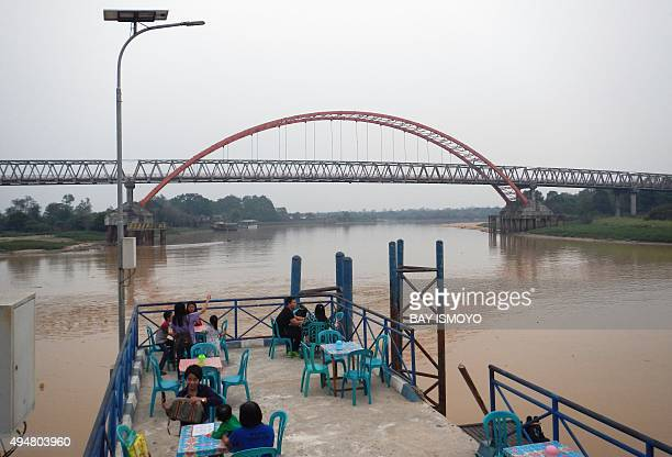 People have dinner at a restaurant near Kahayan river in Palangkaraya in Central Kalimantan on October 29 2015 as residents enjoy clearer skies after...