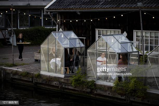TOPSHOT People have dinner in a socalled quarantine greenhouses in Amsterdam on May 5 2020 as the country fights against the spread of the COVID19...