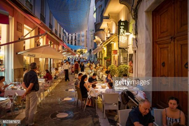 people have dinner in downtown malaga andalusia spain - spain stock pictures, royalty-free photos & images