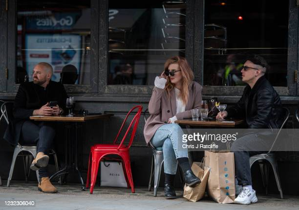 People have drinks outside a bar, with shopping bags at their feet, in Soho on April 14, 2021 in London, United Kingdom. England has taken a...