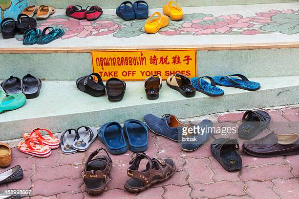 714eba843660 People have left their shoes outside buddhist temple before entering.