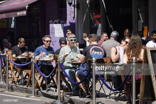 People have lunch at tables outside a restaurant in central London on June 3, 2021. - The UK government are set to decide on June 14 whether their...